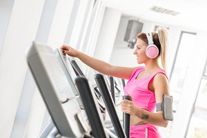 Woman starting crosstrainer workout in a gym.