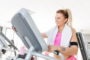 Young woman starts treadmill running.