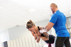 Personal trainer working with a client at the gym.