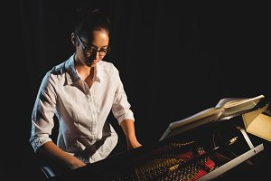 Woman playing a piano in music studio