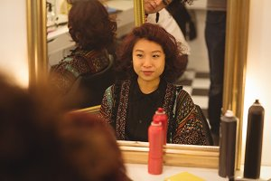 Smiling woman sitting in front of the mirror
