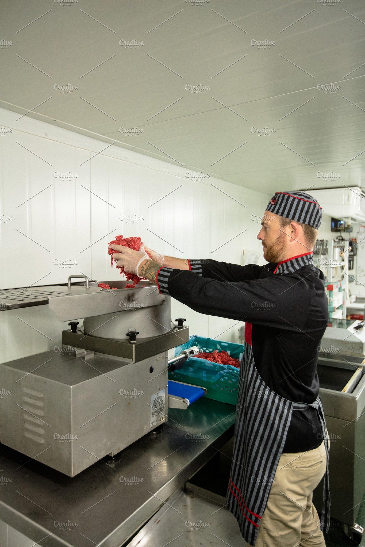 Butcher putting meat in mincer machine