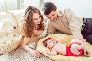 naked baby with her parents