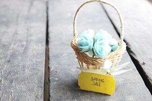 Spring sale tag and flowers in a small basket, copy space. Composition on the old table.