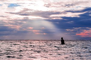 Man silhouette in the sea with ray of sun light