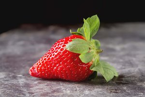Fresh red strawberry with green leaves. Dark background. Ingredients for smoothies.