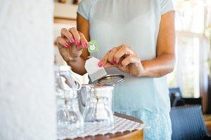 Woman putting tea bag to cup