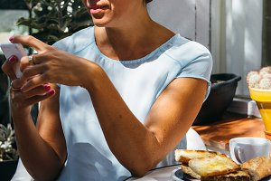 Woman browsing phone having breakfast