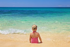 Child sitting on the ocean beach