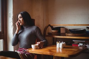 Woman talking on mobile phone while having cup of coffee