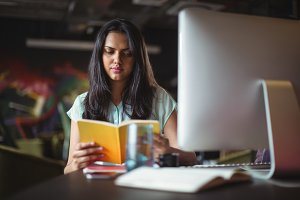 Businesswoman reading book at her desk