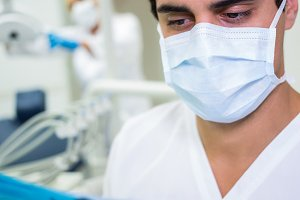 Dentist in surgical mask looking at a medical file