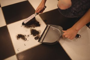 Hands of female staff using dustpan to clean hair waste