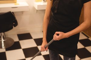 Female hairdresser cleaning hair waste on floor