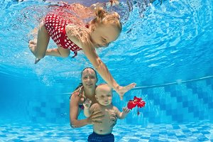 Children swimming with mother