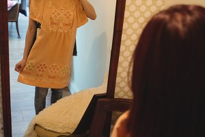 Woman looking at mirror while trying a dress