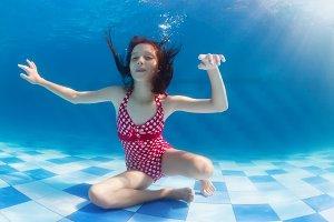 Girl swim underwater in the pool