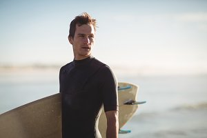 Surfer standing with surfboard