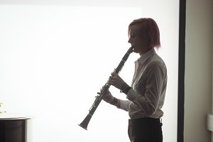Woman playing a clarinet in music school
