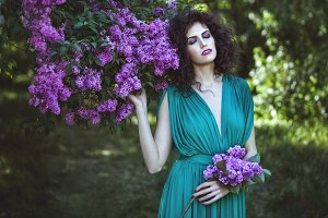 Woman in the bushes of lilac.