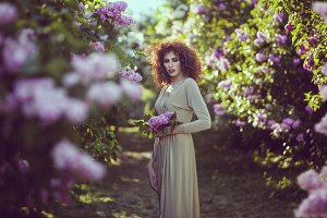 Woman in the alley of lilac bushes in the garden.
