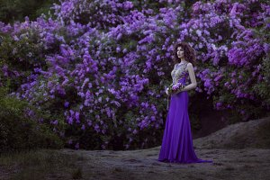Woman on a background of blooming lilac flowers.