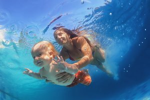 Mother with child dive underwater