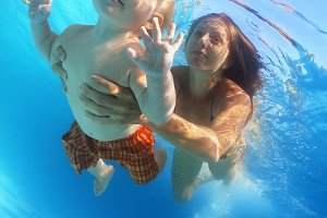 Mother with baby swim underwater