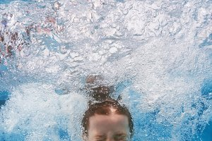 Child jump underwater in pool