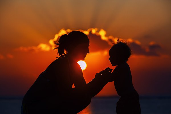 Mother with son on sunset beach