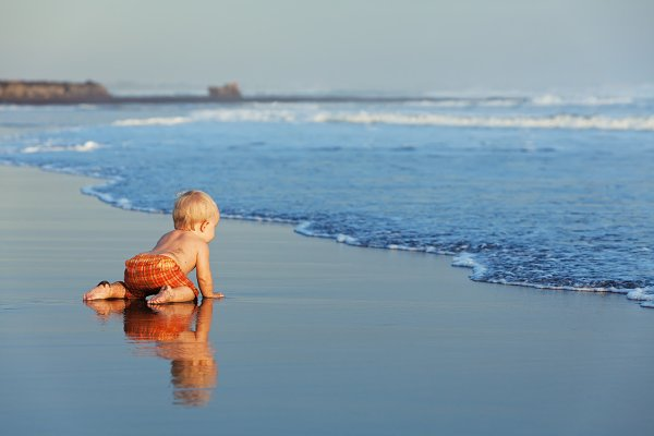 Child crawling on the beach