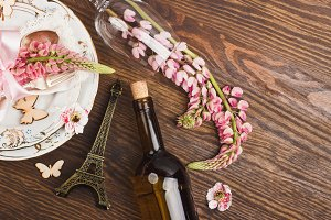 Tableware and silverware with light pink lupins on the wooden background