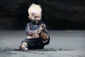 Dirty child play on black sand beach