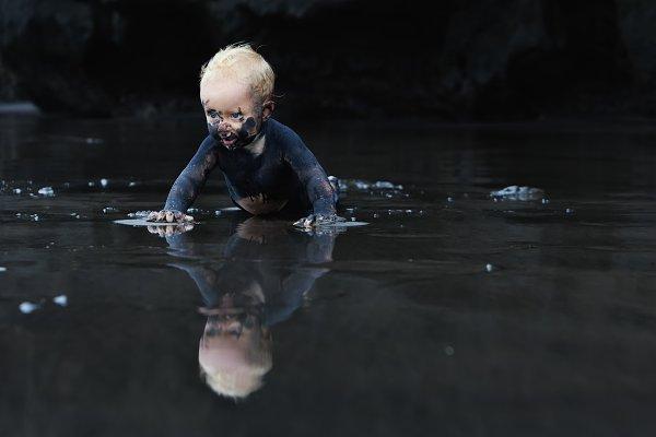 Dirty child on black sand beach