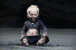 Dirty child play on black sand beach
