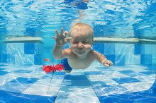 Baby dive underwater in blue pool
