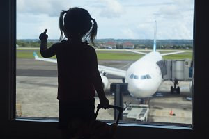 Child in airport look at airplane