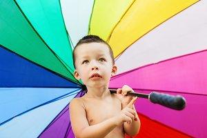 Child under colorful umbrella