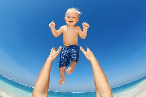 Father tossing up baby on sea beach