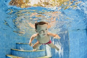 Boy dive underwater in swimming pool