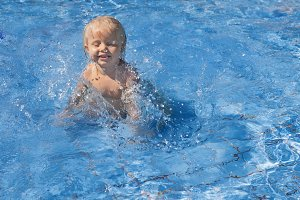 Child splashing in swimming pool