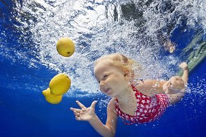 Child with fruits in swimming pool