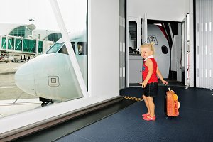 Child boarding to plane in airport