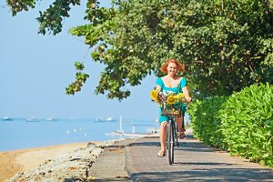 Woman bicycling along sea beach