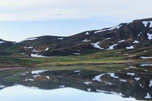 Mountain lake with melting snow