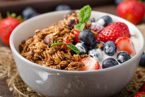 Yogurt with baked granola and berries in small bowl
