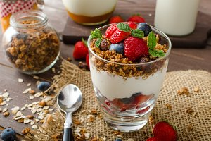 Yogurt with baked granola and berries in small glass