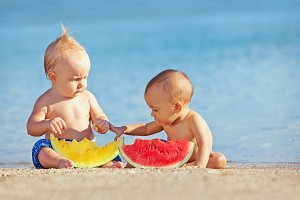 Children with watermelons on beach
