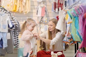 Mother and daughter choose a dress in a children's store
