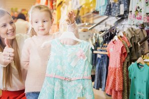 Little girl shows the selected blue dress